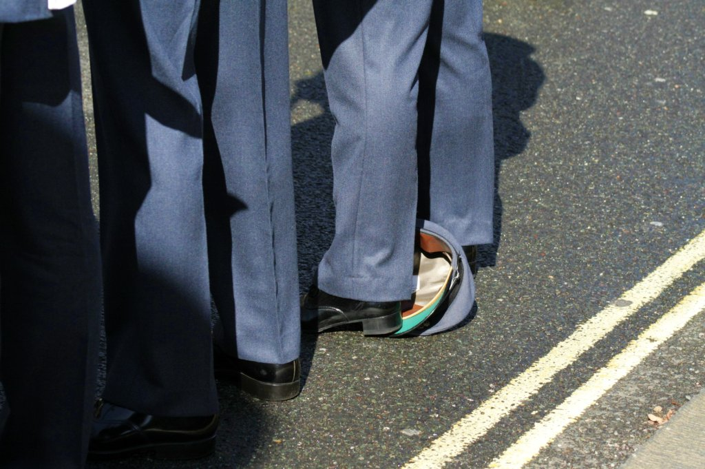 picture of military hat trampled underfoot in the road